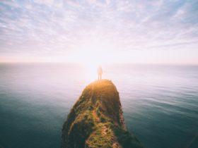 Licht am Horizont: Person steht auf einem Felsen über dem Meer, im Hintergrund geht die Sonne über dem Meer auf