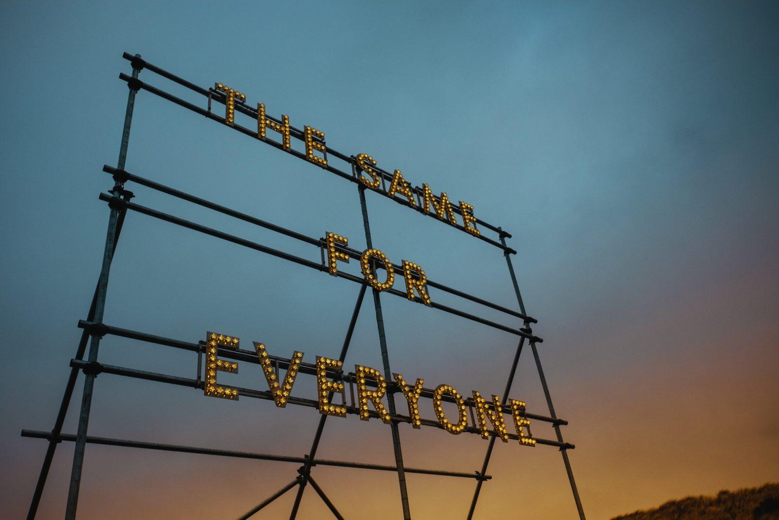 Leuchtreklame mit Schriftzug 'The Same for Everyone' vor einem Abendhimmel